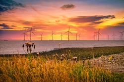 Offshore Wind Turbine in a Wind farm under construction off the England coast at sunset
