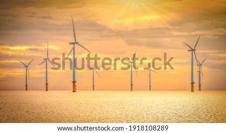 Offshore Wind Turbine in a Windfarm under construction off the England Coast at sunset