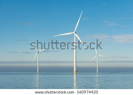 Offshore Windmill farm in the ocean  Westermeerwind park 3 windmills isolated at sea on a beautiful bright day Netherlands Flevoland Noordoostpolder January 2017