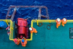 Offshore workers consist of riggers preparing to perform anchor handling on a construction barge at oil filed