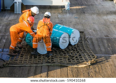 Offshore workers handling lubricant drum to be lifted on a cargo net at construction barge