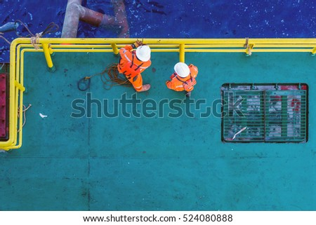 Offshore workers tying ropes to handrail in preparation for anchor handling activity on a bow of a construction barge
