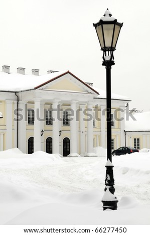 Oginski Palace in Siedlce, Poland covered with snow in winter with street light in the foreground