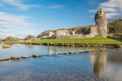 Ogmore Castle, A ruined norman castle near Bridgend, south Wales.  The castle is reflected on the smooth water of the river Ogmore.