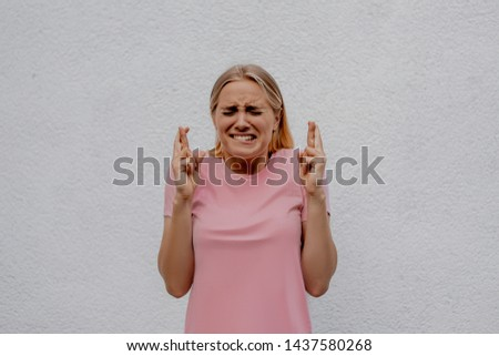 Oh God, please! I hope you! Pleased attractive young woman makes wish to win, raises hands with crossed fingers, waits for lottery results, closes eyes isolated over white wall street background.