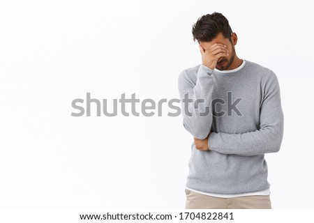 Oh god why me, so lame. Exhausted and bothered handsome male model in grey sweater, make face palm, hiding eyes with palm, bend head down frustrated and upset, humiliated or embarrassed Photo stock ©