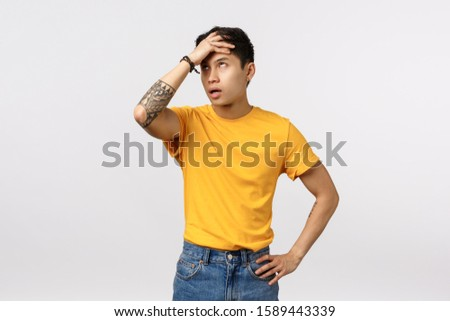 Oh gosh so stupid. Annoyed and pissed young handsome asian guy in yellow t-shirt, punch his forehead, make facepalm and roll eyelids from irritation hear something dumb, white background