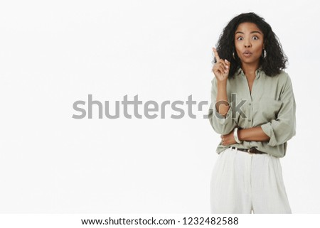 Oh got new idea listen. Energized smart and creative female working in team raising index finger in eureka gesture got awesome plan adding suggestion folding lips in excitement over gray wall
