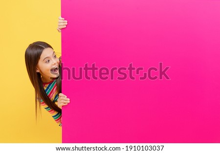 oh my god. child behind paper sheet. place for useful information. place for promotion and creativity. for your marketing design. surprised teen girl with paper banner. kid make announcement. Foto stock ©