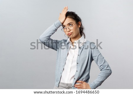 Oh my god, so lame. Tired and annoyed asian woman, teacher having troubles with online education app, punch forehead, facepalm sighing heavily and roll eyes irritated, stand grey background Photo stock ©