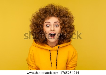 Oh my god, wow! Portrait of surprised curly-haired woman in urban style hoodie looking at camera with mouth open in amazement, expressing shock, astonishment. indoor studio shot, yellow background Photo stock ©