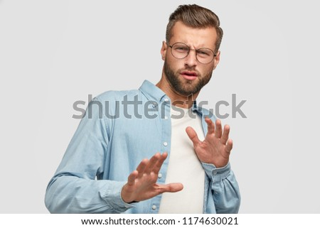 Oh no, dont bother me about this question. Displeased European man makes refusal gesture, keeps hands in front, feels aversion, says its forbidden, dressed in casual clothes, isolated on white #1174630021