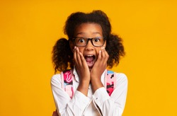 Oh No, School. Scared Afro Elementary Student Girl Screaming Looking At Camera On Yellow Background. Studio Shot, Empty Space