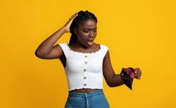 Oh No. Shocked Black Woman Looking At Empty Wallet In Her Hands And Touching Head, Suffering From Poverty And Absence Of Money, Concerned African Lady Standing On Yellow Studio Background, Copy Space