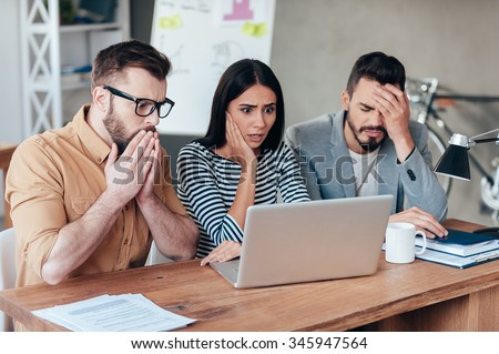 Oh no! Three frustrated young business people in smart casual wear looking at the laptop and expressing negativity