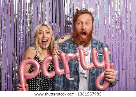 Oh no, what giant party we organized! Surprised happy young woman and man have housewarming celebration, invite many friends, pose in festive clothes with letter shaped balloons. Entertainment