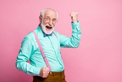 Oh yeah. Profile photo of funky grandpa raise fists celebrating ecstatic good mood wear specs mint shirt suspenders violet bow tie pants isolated pink pastel color background