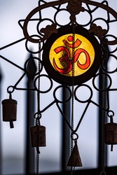 ohm sign on glass and metal chimes
