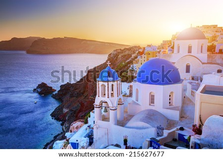 Oia town on Santorini island, Greece at sunset. Traditional and famous churches with blue domes over the Caldera, Aegean sea #215627677