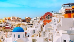 Oia town on Santorini island, Greece. Traditional and famous houses and churches with blue domes over the Caldera, Aegean sea.