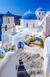 Oia town, Santorini island, Greece. Traditional and famous white houses and churches  with blue domes over the Caldera, Aegean sea.