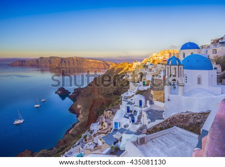Oia village in the morning with dusk sky colors Santorini, Greece - Oia at morning, Santorini, Cyclades, Greece, Building lit up after sunrise in Oia, Santorini, Greece