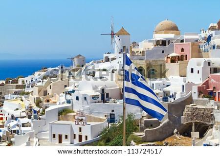 Oia village scenery with Greek flag on Santorini island
