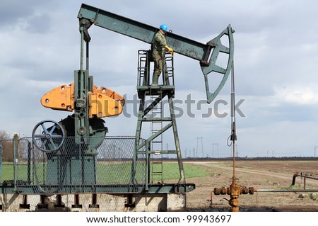 oil and fuel industry oil worker standing on the pump jack