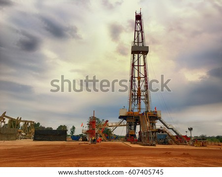 Oil and gas drilling rig onshore dessert with dramatic cloudscape