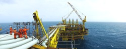 Oil and gas industries. Panorama view of offshore scaffolders standing on the pipeline and new oil and gas platform installed in the middle of the sea with cloudy sky background.