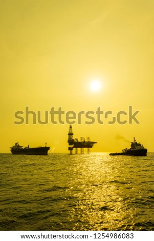 oil and gas industry. A golden hour with silhouette of oil and gas tripod jack up rig, Floating Storage Offloading (FSO) vessel and support vessel in the middle of the sea. #1254986083