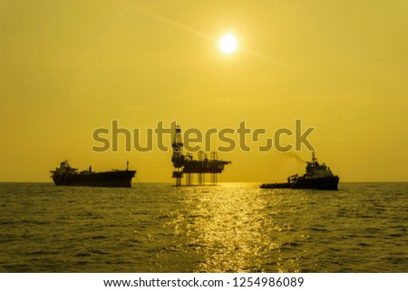 oil and gas industry. A golden hour with silhouette of oil and gas tripod jack up rig, Floating Storage Offloading (FSO) vessel and support vessel in the middle of the sea. #1254986089
