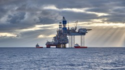 Oil and gas industry in the North Sea. View of Jack up drilling platform with supply vessels in the sea.