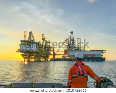 Photo of  Oil and gas industry. Marine crew standing on supply vessel looking oil and gas platform during sunrise.