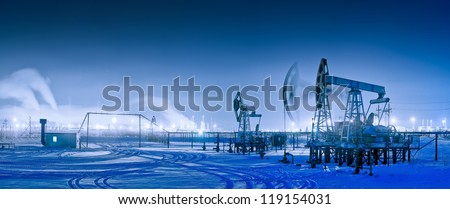 Oil and gas industry. Panoramic of a pump jack and oil refinery in the winter with snow. Night view.