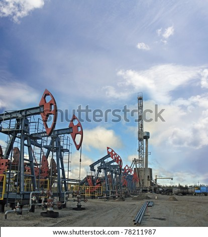 Oil and gas industry. Work of oil pump jack and rig on a oil field.