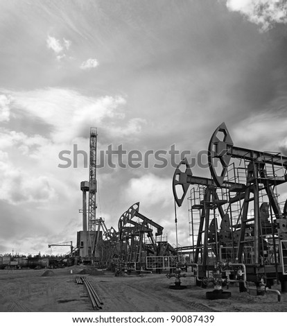 Oil and gas industry. Work of oil pump jack and rig on a oil field. Mining and drilling. Black and white photo