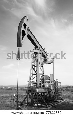 Oil and gas industry. Work of oil pump jack on a field. Environment damage. Black and white photo