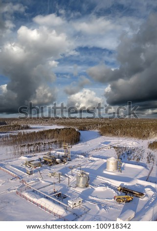 Oil and gas industry. Work of oil pump jack on a oil field.. Construction site in wild winter forest. Building of petrochemical plant