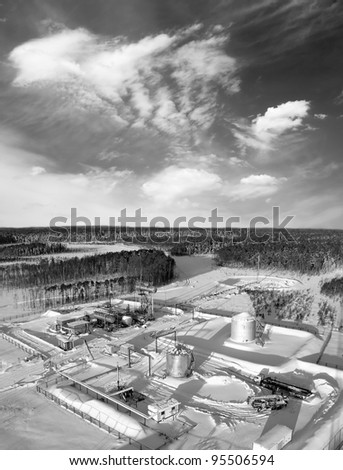 Oil and gas industry. Work of oil pump jack on a oil field. Construction site in wild winter forest. Building of petrochemical plant. Black and white photo.