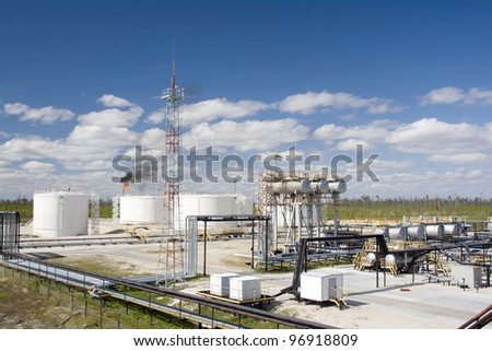 Oil and gas industry. Work of refinery petrochemical plant. Oil reservoir and storage tank of mineral oil. Flame torch