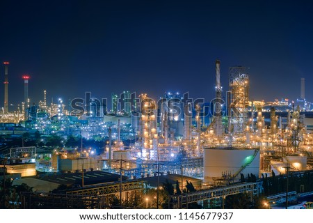 Oil and Gas refinery industry plant with glitter lighting, Factory of petroleum industrial at night time, Petrochemical plant with gas distillation tower and storage tank #1145677937