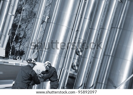 oil and gas workers, hardhat, large shiny pipes in background, slight blue toning concept - stock photo