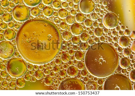 oil and soap mix in water, oil droplets background.