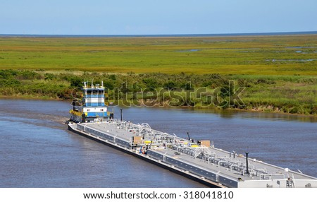 Oil barge being pushed through waterway by a tugboat