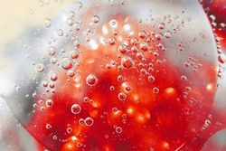 Oil bubbles close up. a circles of water macro. abstract blue and fiery red background