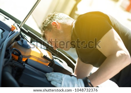 Oil change in car. Man repairing the engine in the car. Self-changing oil in own car. Man looks under the hood of his auto. Auto repair. Auto Mechanic. #1048732376