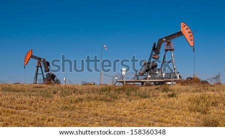 Oil dereks in a wheat field in Alberta, Canada. Stock fotó ©