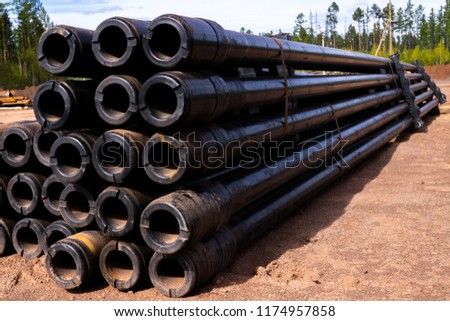 Oil Drill pipe. Rusty drill pipes were drilled in the well section. Downhole drilling rig. Laying the pipe on the deck. View of the shell of drill pipes laid in courtyard of the oil and gas warehouse.