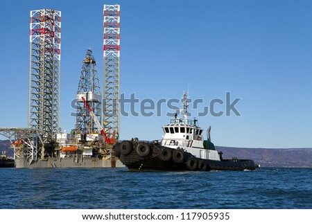 Oil drilling jack up rig with a tug boat in the Kachemak Bay near Homer Alaska on a sunny day.